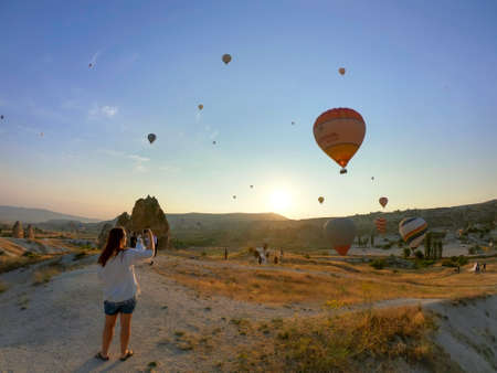 lady taking pictures of hot air balloons in cappadocia at sunrise Editorial