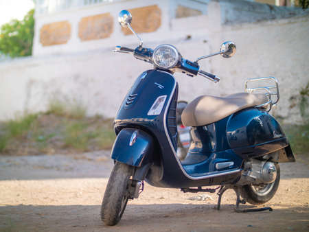 a parked blue vespa on dirt in Greece