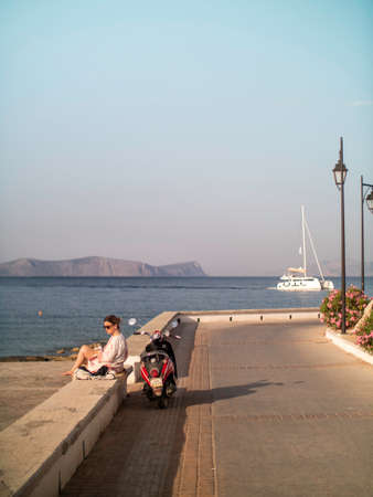 Lady sitting watching the ocean with vespa on Spetses