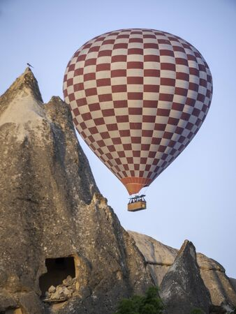 red and white hot air balloon flying over cave house in cappadocia