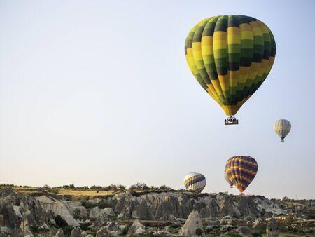 several hot air balloons rising over the Cappadocia desert
