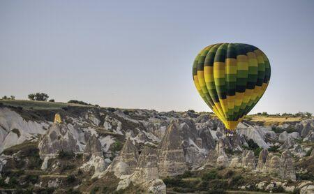 a brightly colored hot air balloon over cappadocia cave homes Standard-Bild