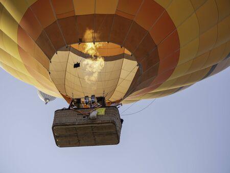hot air balloon flames to gain height over cappadocia