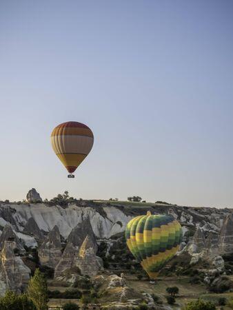 two hot air balloon tours rising over the Cappadocia desert
