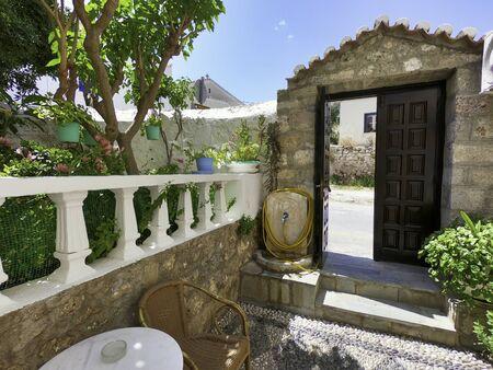Heavy wooden door and a garden patio in Greece Standard-Bild