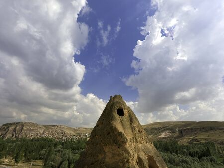 cave house at the top of a sandstone spire with huge clouds
