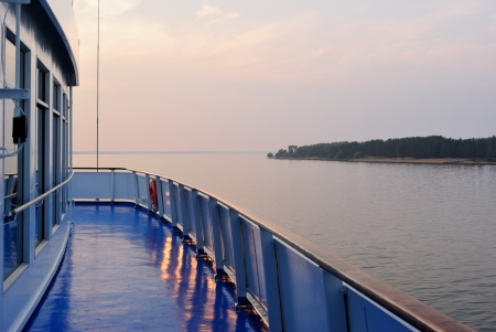 onboard: Summer sunset seen from a deck of a cruise liner  Shot at Rybinsk water reservoir  informally called the Rybinsk Sea  on the Volga River
