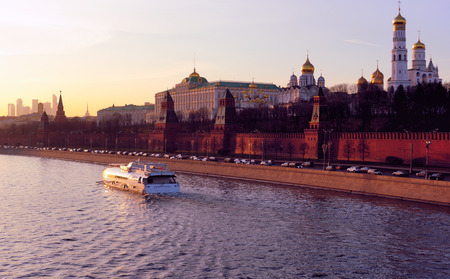 Moscow, Russia – February 26, 2014 - Moscow Kremlin and Moskva river  with a pleasure boat  seen from Bolshoy Moskvoretsky Bridge in the evening