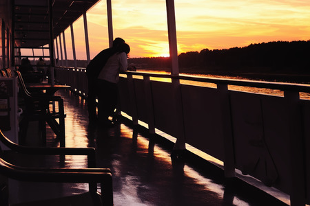 cruise liner: Couple Looking at Sunset on the Deck of a Cruise Liner Sailing along a River