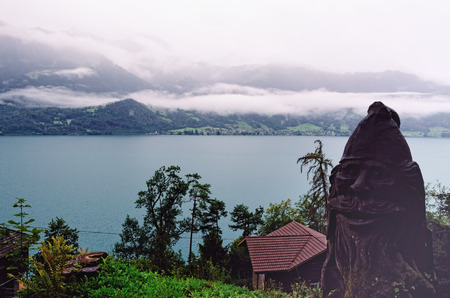 lived here: View of Lake Thun from a Waterfall at the Entrance to Saint Beatus Caves on Lake Thun in Beatenberg Municipality, Interlaken District, Canton of Bern, Switzerland. Sculpture of a Dwarf alludes to the Legends of Dwarves who lived here