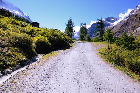 wooded path: Mountain Road in Swiss Alps between Matterhorn Mountain and Resort Town of Zermatt, Canton of Valais, Southern Switzerland Stock Photo