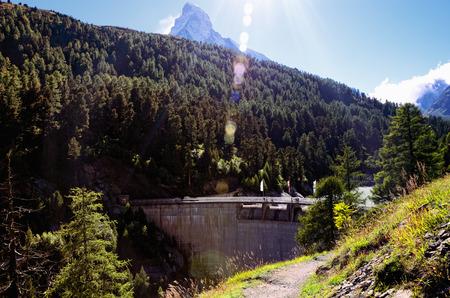 wooded path: Dam in Swiss Alps on Zmuttbach River in Zmutt Valley near Resort Town of Zermatt, Southern Switzerland, and Matterhorn Mountain in Sun Flares in the Background Stock Photo