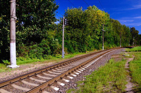 Railway Line Going into the Distance among Green Summer Grass and Foliage; Clear Blue Sky in the Background Stock Photo