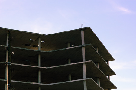multi story: Top of a Multi-Story Apartment Building in the Process of Construction, with Blue Sky in the Background