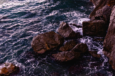 Foaming Sea Waves Breaking against Coastal Rocks