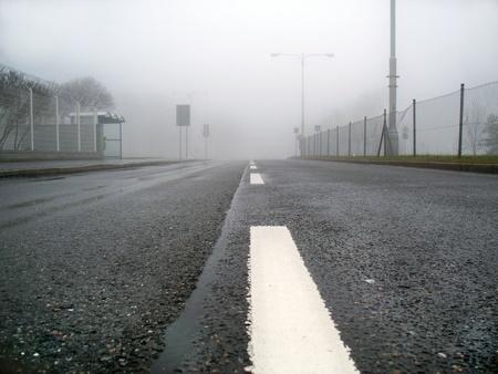 single lane road: Asphalt road in the fog leading to nowhere