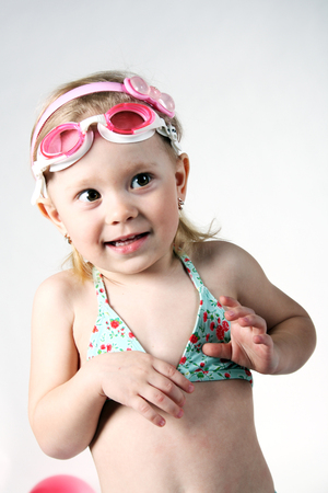 cute smiling little child in swimsuit and swim glasses