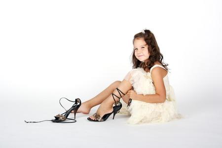 그녀의 어머니의 신발을 시도하는 어린 소녀