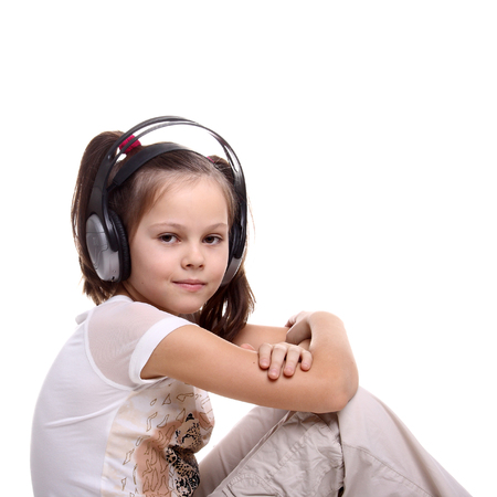 audition: beautiful little girl in headphones isolated on white Stock Photo