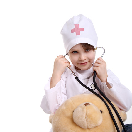 pretty little girl playing a doctor with her toy bear
