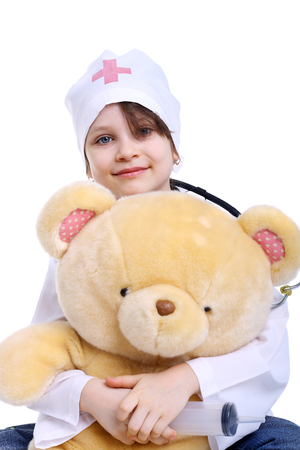 smiling little girl playing a doctor with her toy bear