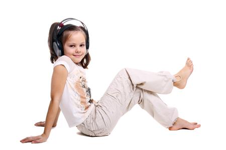 beautiful little girl in the headphones sitting on the floor