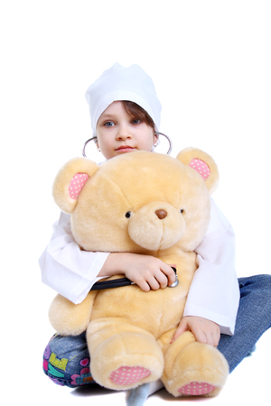 smiling little girl playing doctor with her toy bear