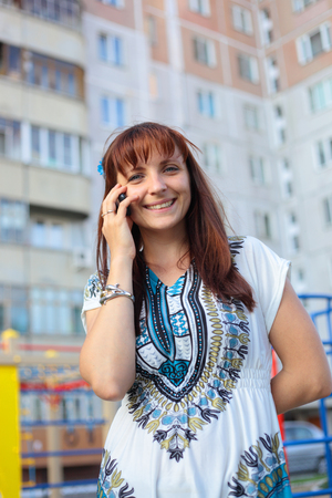 pretty smiling young woman speaking a mobile phone outdoors
