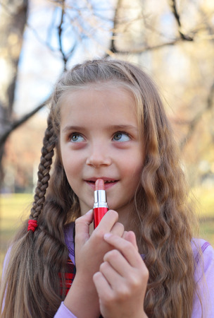 smiling little girl putting on the lipstick