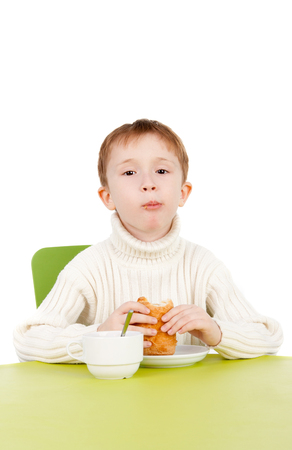 closeup image of the handsome little boy eating a snack near the table
