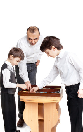 two little boys and their father playing backgammon Stock Photo