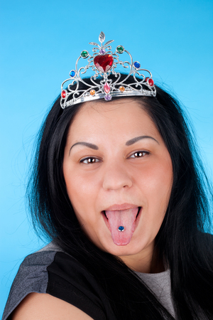 closeup image of the pretty young girl in the diadem over the blue background showing her tongue with the piercing