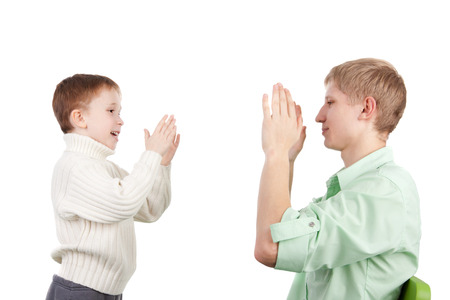 cute little boy playing pat-a-cake with his elder brother