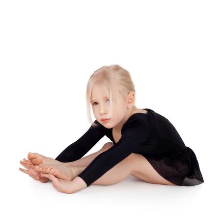 kleine gymnast doet de gymnastische oefeningen Stockfoto