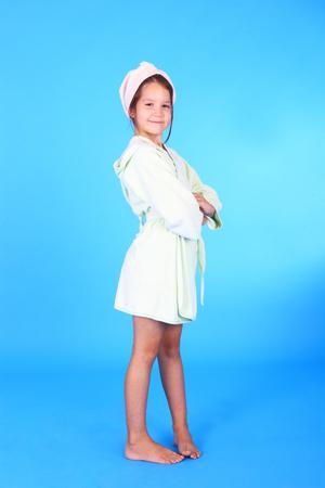 hübsches kleines lächelndes Mädchen im Bademantel Standard-Bild