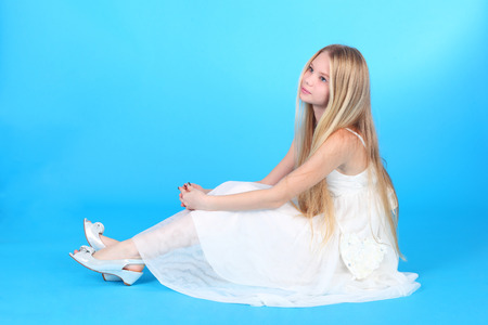 pretty teenage blond girl in the white dress over the blue background