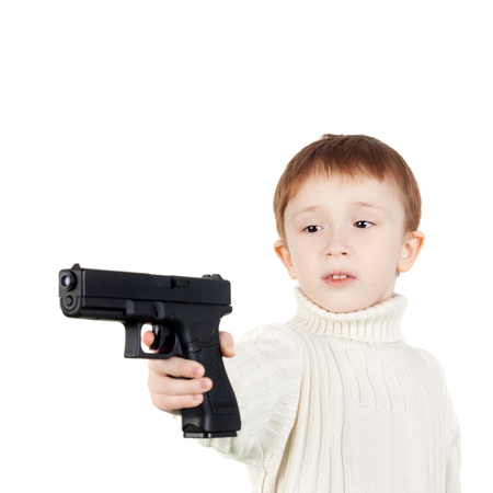 serious little boy with the big black pistol Stock Photo
