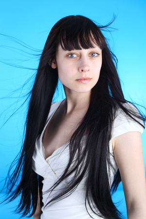 beautiful young brunette girl with windy hair over blue background Reklamní fotografie