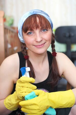 pretty smiling young girl cleaning the house