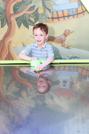 happy little boy playing air hockey