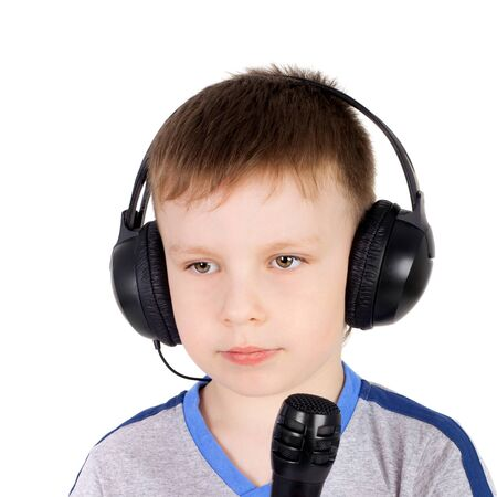 cute sweet little boy in the headphones with the microphone singing karaoke Stockfoto