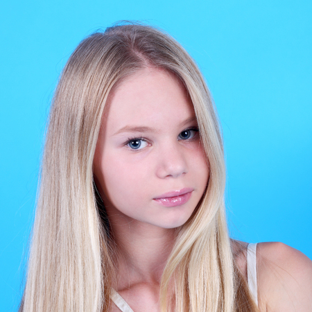 showy blond teen girl on the blue background closeup Foto de archivo