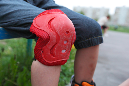 little roller skater putting on the protective knee-pad