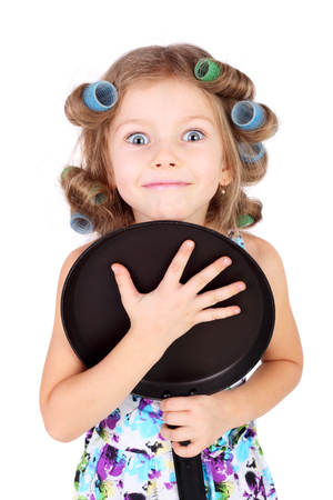 cute funny little girl wearing the curler and with the pan