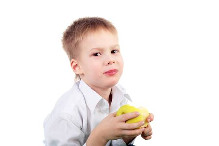 smiling little boy eating the big yellow apple