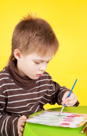 closeup image of the cute little boy painting on the yellow background