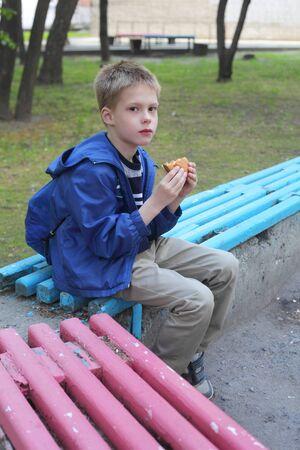 little boy eating hamburger in the park