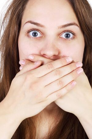 closeup image of the very surprised girl with her hands on her mouth