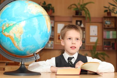 little boy reading book in the classroom Stock Photo