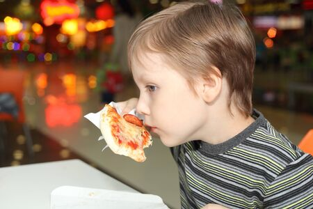 cute little boy smelling pizza 스톡 콘텐츠
